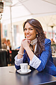 Pretty woman enjoying a coffee in a Cafe, smiling at camera