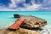Wooden bridge across rocks on the coastline of Cancun. Erosion and rock formatons. Planks. Caribbean sea.