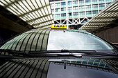 Taxi cab emerging from a tunnel underneath an office building. A front view, with a yellow taxi light on the roof of the car. Reflection on the windscreen of sky and buildings.