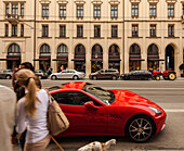 Red Ferrari and tractor in Maximilian street, shopping girl with dog, Munich, Upper Bavaria, Bavaria, Germany