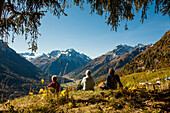 A family, two girls, a younger and an older woman sit on a meadow, autumn at Guarda, Engadin, Graubuenden, Grisons, Switzerland