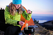 Young woman cooking noodles beside a tent, Risserkogel, Bavarian Prealps, Mangfall Mountains, Bavaria, Germany