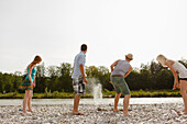 Young people dapping stones at the Isar river, Munich, Bavaria, Germany