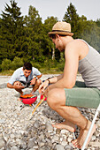 Two young men barbecueing at the Isar river, Munich, Bavaria, Germany