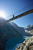 Hiker walking across a suspension bridge over a mountain lake, Trift glacier in the background, Trift glacier suspension bridge, Tieralplistock, Urner Alps, Bernese Oberland, Bern, Switzerland