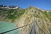 Suspension bridge across a mountain lake, Trift suspensin bridge, Trift glacier, Tieralplistock, Urner Alps, Bernese Oberland, Bern, SwitzerlandT