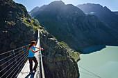 Woman standing on a suspension bridge over a mountain lake, Trift suspension bridge, Trift glacier, Tieralplistock, Urner Alps, Bernese Oberland, Bern, Switzerland