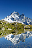Mont Blanc range with Aiguille Verte and Grand Dru reflecting in a mountain lake, Mont Blanc range, Chamonix, Savoy, France