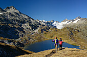 Woman and man hiking near a mountain lake with view to Oberaarhorn and Finsteraarhorn, Bernese Alps, Bernese Oberland, UNESCO World Heritage Site Swiss Alps Jungfrau-Aletsch, Switzerland