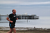 Jogger at the promenade in front of the pier of seaside resort Llandudno, North Wales, Great Britain, Europe