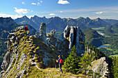 Two hikers descending along a ridge of Tegelberg, Tannheim range in the background, Tegelberg, Ammergau range, Allgaeu, Swabia, Bavaria, Germany