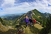 Young woman and two young men ascending on a ridge to Aggenstein, Aggenstein, Tannheim range, Tyrol, Austria