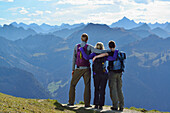 Young woman and two young men enjoying the view from Aggenstein Allgaeu range, Aggenstein, Tannheim range, Tyrol, Austria