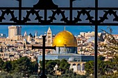 The Dome on the Rock on the Temple Mount, viewed through an ornate window with a cross in the Sanctuary of Dominus Flevit Roman Catholic church on the Mount of Olives, Jerusalem, Israel