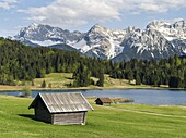 The Karwendel Mountain Range near Mittenwald during spring, lake Wagenbruch also called Geroldsee The green pasture is in a strong contrast with the still snow covered peaks of the western Karwendel mountains towering above Mittenwald The Karwendel mounta