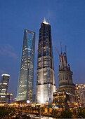Evening view of World Financial Center left JinMao Tower center and Shanghai Tower under construction in Lujiazui Pudong Shanghai China
