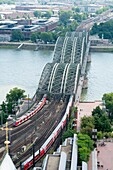 View from above of Hohenzollern Bridge across River Rhine at railway station in Cologne Germany