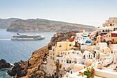 View of waterside clifftop buildings and the Norwegian Jade cruise ship, Oia, Santorini, Greece