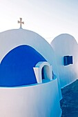 a private chapel in Greece with a dome, cross, and attached dwelling