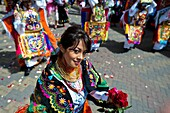 A dancer danzante, holding flowers, performs in the religious parade within the Corpus Christi festival in Pujilí, Ecuador, 10 June 2012  Every year in June, thousands of people gather in a small town of Pujili, high in the Andes, to celebrate the Catholi