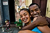 A young Cuban boy embracing a girl on the street of Santiago de Cuba, Cuba, 29 July 2008  Cubans are generally very warm and joyful people  About 50 years after the national rebellion, led by Fidel Castro, and adopting the communist ideology shortly after