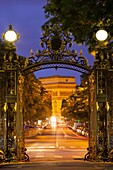 Arc de Triomphe framed by the entry gates to Parc Monceau, Paris France