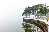 The barrier wall on a desolate and foggy West Lake in Hanoi, Vietnam