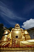 Large and laughing golden Buddha statue against a deep vivid blue summer sky  Khao Takiab temple Hua Hin Thailand S E  Asia