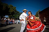 A young couple wearing traditional dresses dance during the Guelaguetza parade in Oaxaca, Mexico, July 21, 2012  Oaxaca commemorates the ´Guelaguetza,´ an annual celebration by all seven of the state´s regions, as they converge on the capital to demonstra