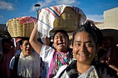 Women smile and carry baskets with food in their heads during the Guelaguetza parade in Oaxaca, Mexico, July 21, 2012  Oaxaca commemorates the ´Guelaguetza,´ an annual celebration by all seven of the state´s regions, as they converge on the capital to dem