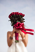 Young Woman Holding Bouquet of Red Roses in Front of Face