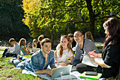 Group of young people learing at Dreisam riverbank, Freiburg im Breisgau, Black Forest, Baden-Wurttemberg, Germany