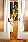 Girl wearing an angel costume looking through a sliding door, christmas tree in background, Hamburg, Germany