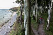 Women cycling through Gespensterwald (ghost forest), Hoellenliet, Wittow Peninsula, Island of Ruegen, Mecklenburg-Western Pomerania, Germany