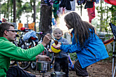 Family on a campsite, father givong food to the children, girl (12 years) and boy (2 years), cooking a meal, camping stove, drying clothes, tree, Cycling trip of a family, summer, Baltic Sea, MR (father and son), rainbow campground near Bakenberg, Wittow
