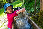 Child washing hands at a fountain, Plankenstein hut, Plankenstein, Rottach-Egern, Bavaria, Germany