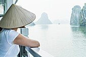 Woman on a wooden junk enjoying the view in Halong Bay, north of Vietnam, Asia