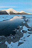 Morning light on the Kenai Mountains reflects on the waters and ice of Turnagain Arm, Southcentral Alaska, Winter. HDR