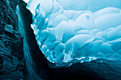 A waterfall trickles its way down the rock face of an ice cave inside the Mendenhall Glacier, Juneau, Southeast Alaska, Summer