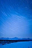 Night time view of star trails over Mt. McKinley with Northern Lights in the background, Denali State Park, Southcentral Alaska, Winter