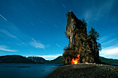 Campfire on the beach at New Eddystone Rock with star trails overhead, Misty Fjord National Monument, Inside Passage, Southeast Alaska, Summer