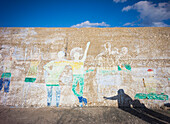A coastal town.  Marina seawall with graffiti images of people. Shadows of two people on the ground.