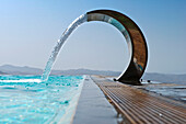 A curved stainless steel water fountain with water flowing into an infinity pool. Hilltop view over mountains.