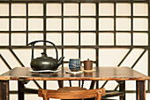 A Chinese style wooden table, with a pottery teapot and cups. A wooden geometric frame wall decoration. Living room in a house.