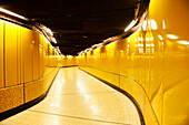 A tiled passageway in the underground Metro station. Vivid yellow colour.   Public transport space.