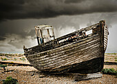 A wooden fishing boat, on the beach at Dungeness. A dark stormy sky.