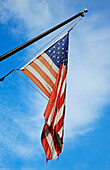 An old tattered frayed flag, the Stars and Stripes national American flag, flying on a flag pole.