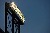 A tall lighting gantry or tower with strong powerful floodlights, over a sports area or stadium.