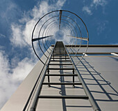 A ladder on the exterior of an industrial building in Estonia, Barbed security wire