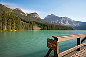 A view from a waterfront pier over the landscape of the Rocky Mountains surrounding the Emerald Lake and the brightly coloured waters of the lake